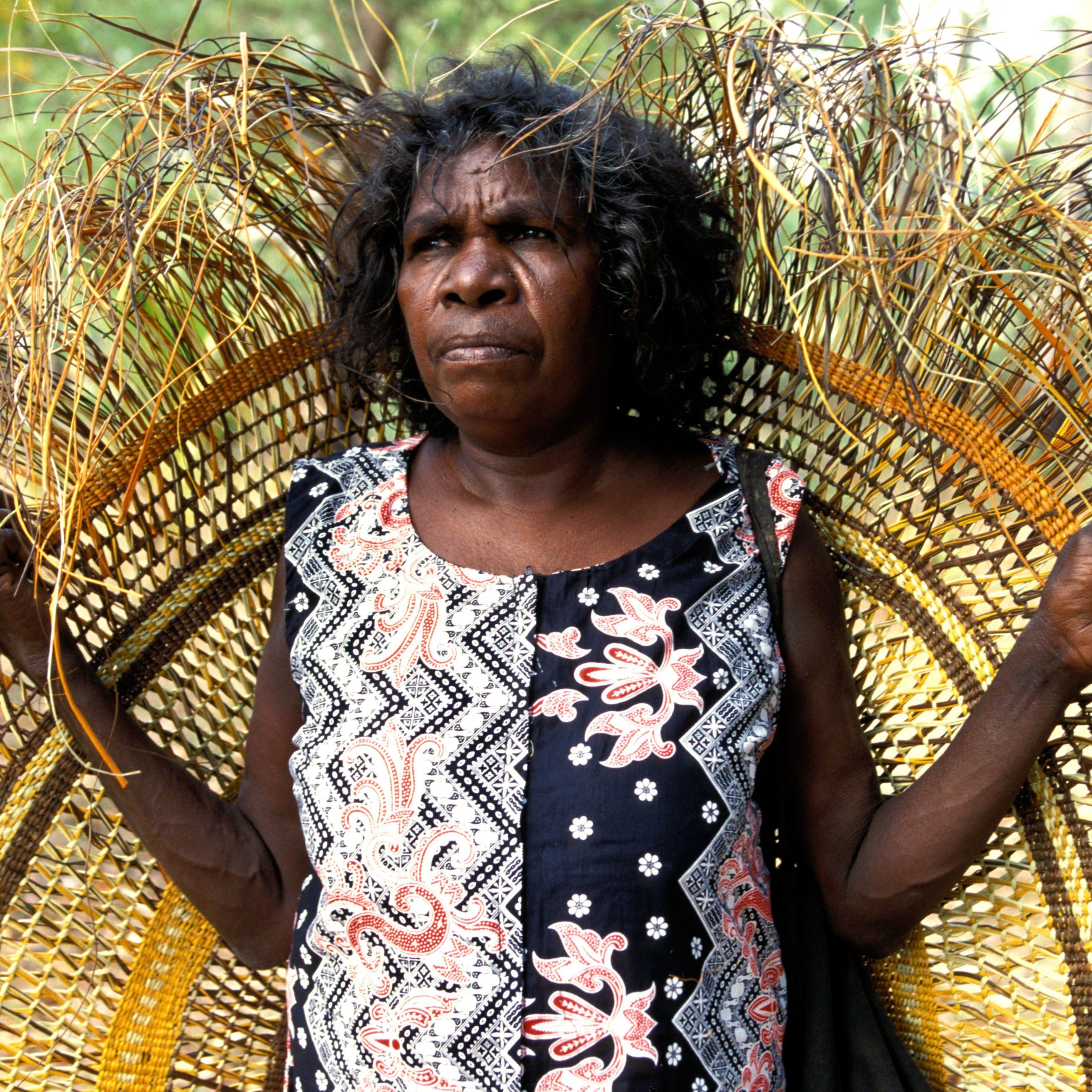 AXCFDE Aboriginal woman artist Judy Baypungnalala with traditional pandanus mat she has woven Ramingining Arnhem Land NT Australia