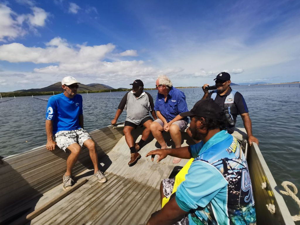 Five men tour an oyster farm in a small boat to explore community development opportunities, one is filming the tour.