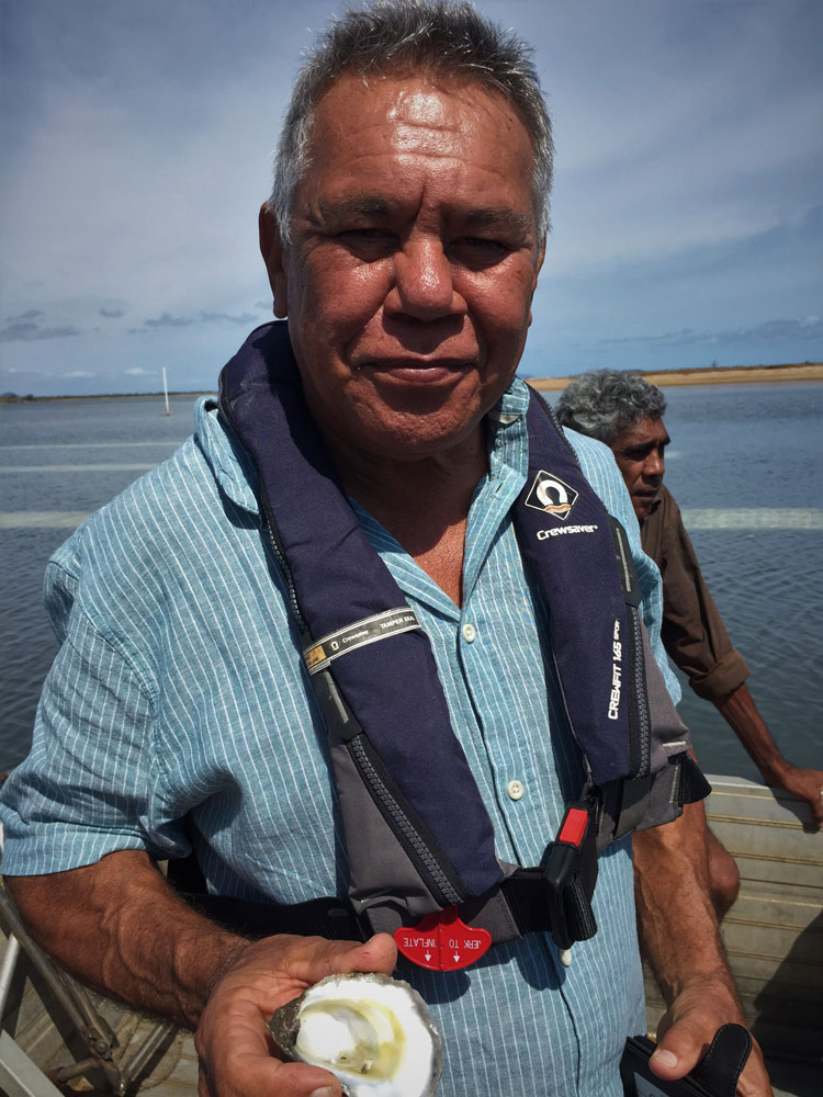 An aboriginal man from shows off a shucked oyster for the camera