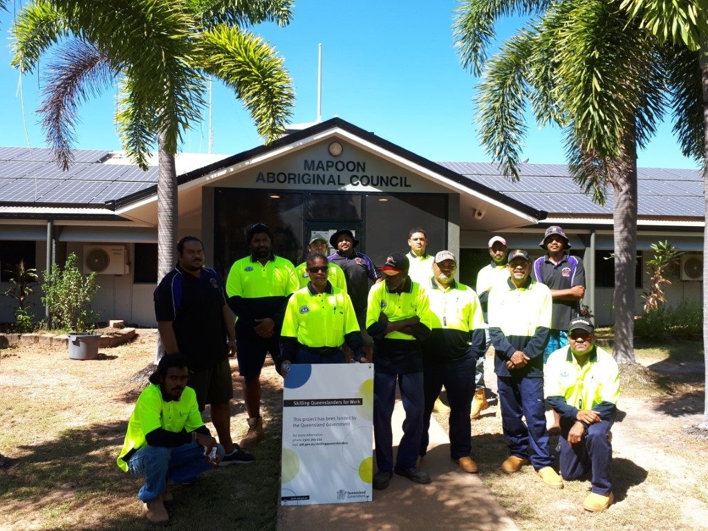 Ten Indigenous construction trainees pose with their three mentors in front of the Mapoon Aboriginal Council building